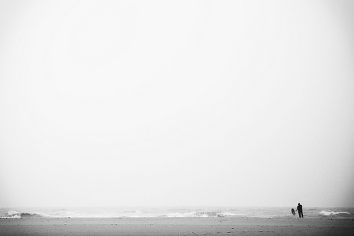 Man with umbrella alone on a beach - minimalist photo using lots of negative space