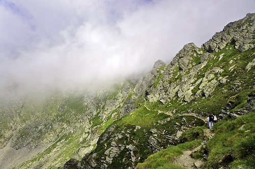 Two hikers on a narrow mountain path, clouds rolling over the edge of the mountain in front of them