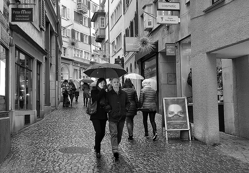 Street photo of couple walking past shops on a rainy day