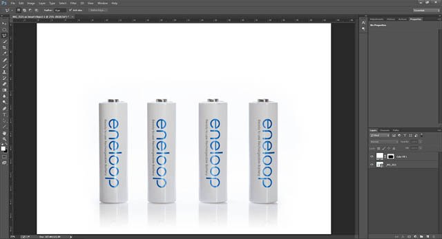 Photo of white batteries on white background being edited in Photoshop, with a white color fill layer partially masked in around the edges