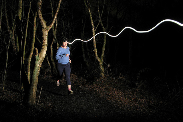 Front / First curtain flash sync example - runner frozen with light trail from their headlamp extending in front of them