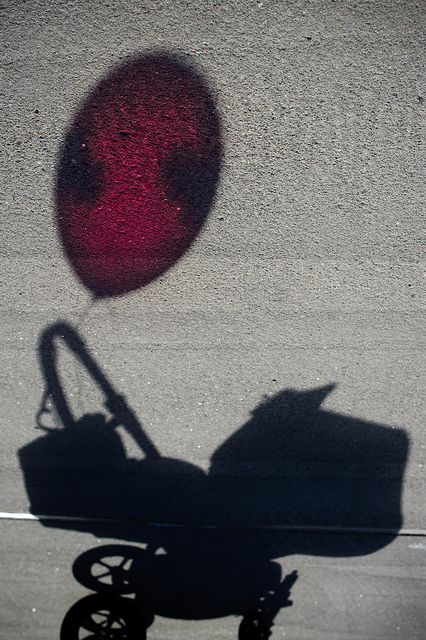 Shadow of a pram with a colored balloon