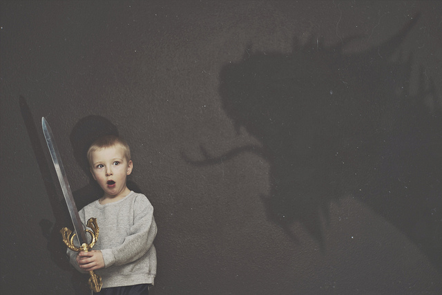 Little boy with a sword and shadow of a dragon