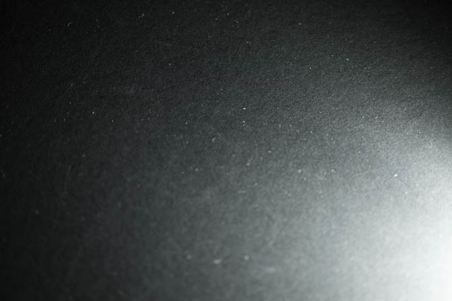 Piece of black card lit by speedlight flash fired at minimum power (1/128)