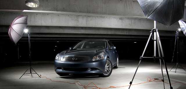 3 studio strobes for car shoot, with power cords for the lights trailing across the floor.