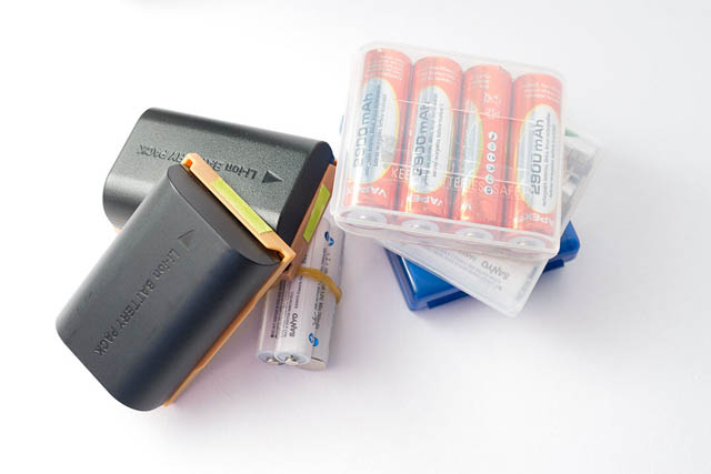 Spare camera batteries, AA batteries, and AAA batteries. The camera battery clips have a green sticker on one end - if the battery is attached in the clip so the arrow on the battery points towards the green sticker, it means the battery is charged and ready to use.