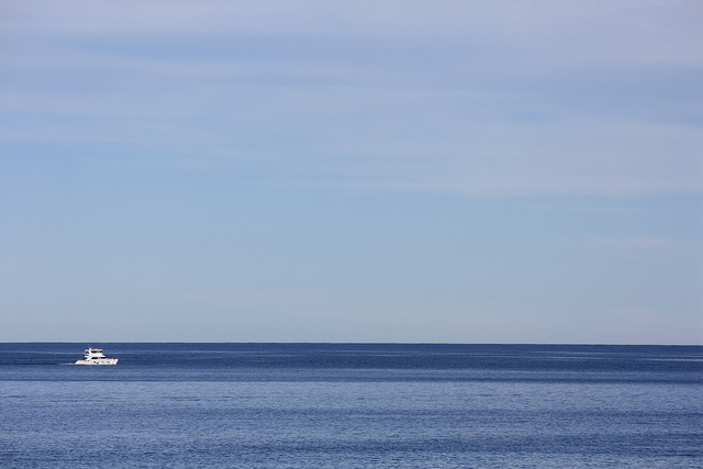 Minimalist photo of a boat on the sea with a large negative space