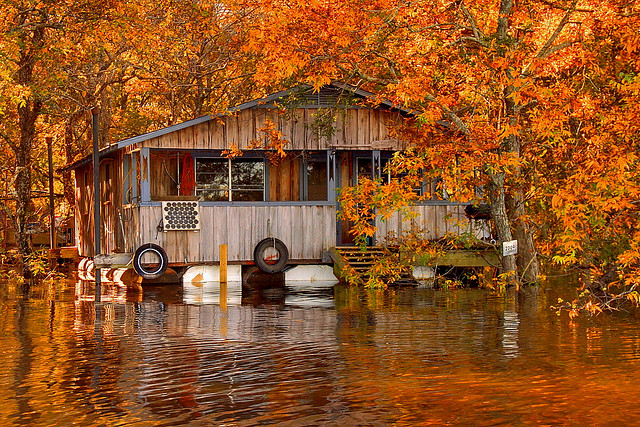 Floating camp on the Ouachita River by FinchLake, fall colors on the trees and reflecting in the river creating an image with very strong saturated colors