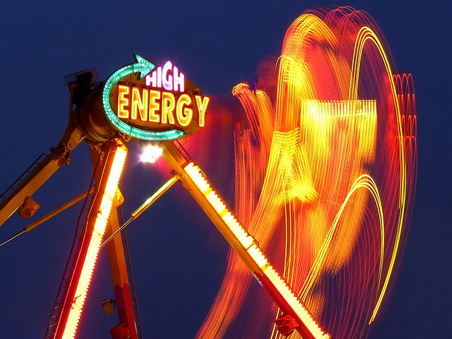 Long exposure of a fun fair ride with the orange lights of the ride leaving trails against the dark blue evening sky