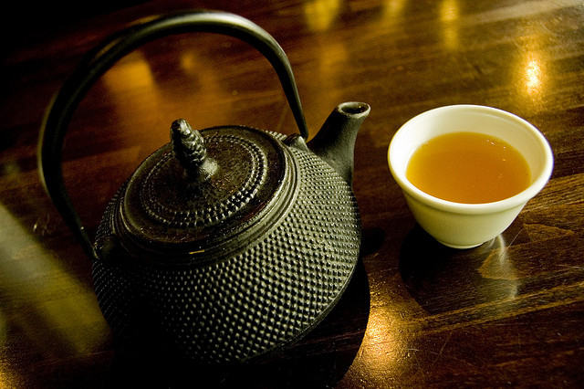 Photo of a cup of tea and teapot on a table using a minimal number of different colors - the table is brown, reflections of lights on the table and tea are orange,  the teapot is black and cup is white (technically black and white are tones, not colors).