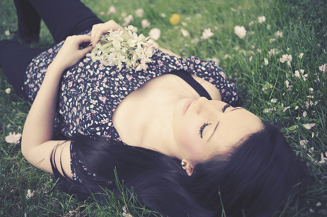 Dreamy portrait using pastel colors of a woman lying on the grass