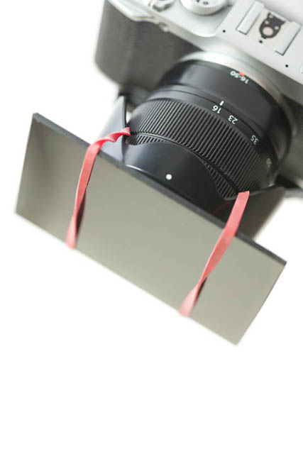 Attaching a welding glass filter (cheap alternative to a strong ND filter for long exposure daylight photography) to a lens using elastic bands and a reversed lens hood.