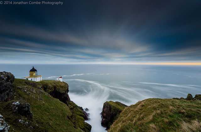 Lighthouse, cliffs, sea, and clouds. The sea and clouds are blurred and smoothed out by the long exposure used for this photo.