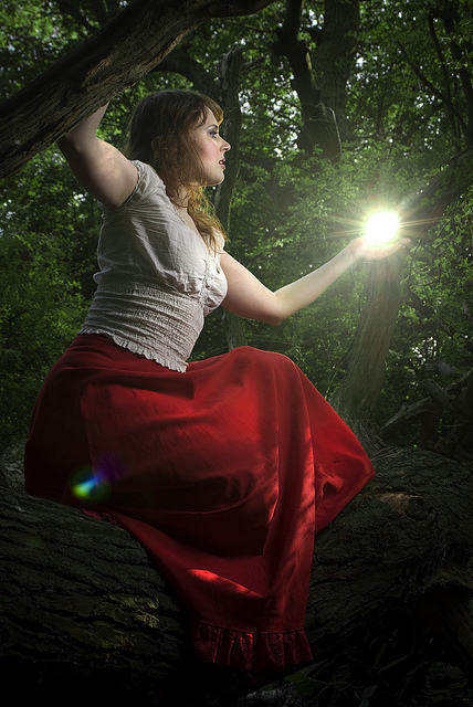 Portrait in forest lit with two off-camera flashes, one to highlight the model, the other positioned within the frame, slightly above her hand, to look like a ball of light in her hand