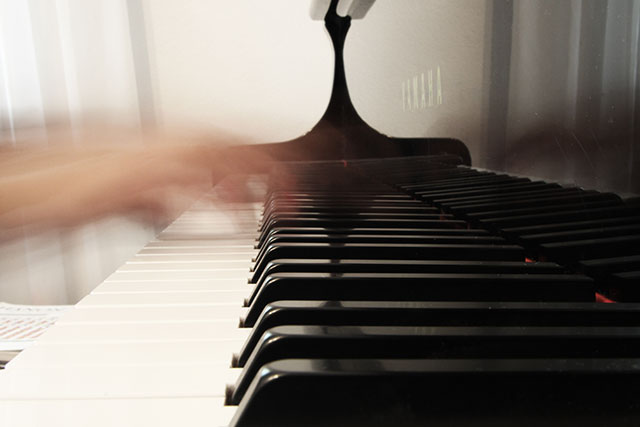 Blurred hands playing the piano, captured using a slow shutter speed