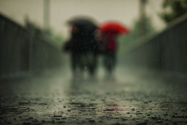 People walking across a bridge in the rain, focus is on the near part of the bridge, not the people.