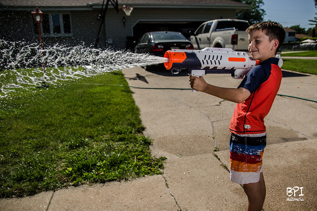 Boy firing a supersoaker water gun outside in daylight. A fast shutter speed combined with high speed sync flash was used to freeze the water while providing a good exposure.