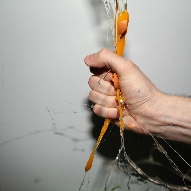 High speed photo of an egg being smashed by squeezing it in the hand