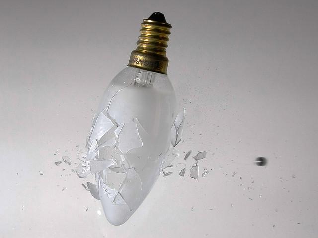 A light bulb smashing as a ball bearing pellet is fired through it