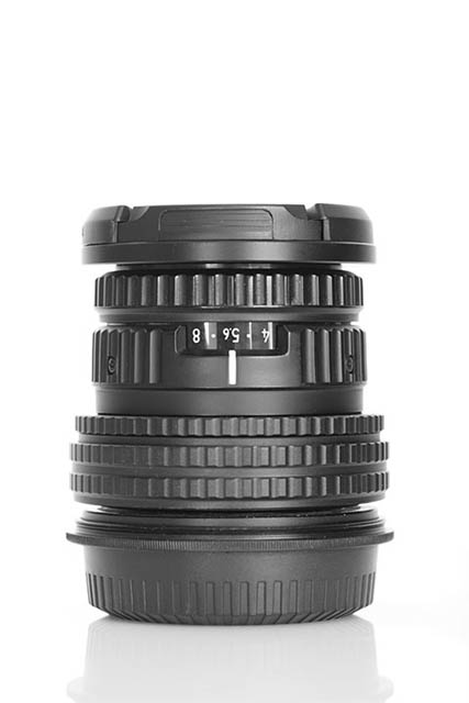 Photo of a camera lens against a white background. It was taken with the background quite close behind the lens, resulting in quite a bit of light from the background spilling forwards around the edges of the lens.