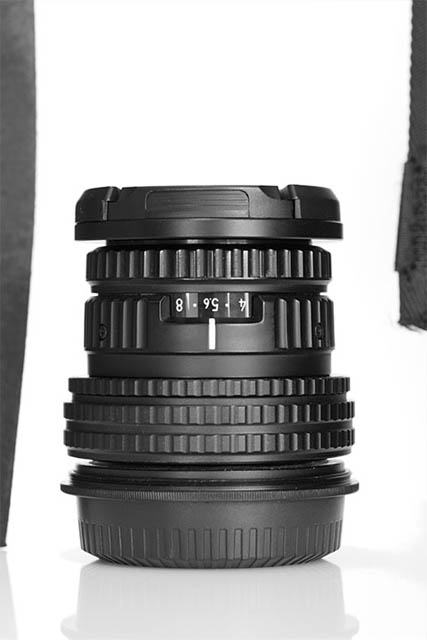Photo of a camera lens against a white background. 'Flags' were placed either side of the lens to reduce the amount of light spill from the background hitting the edges of the lens.