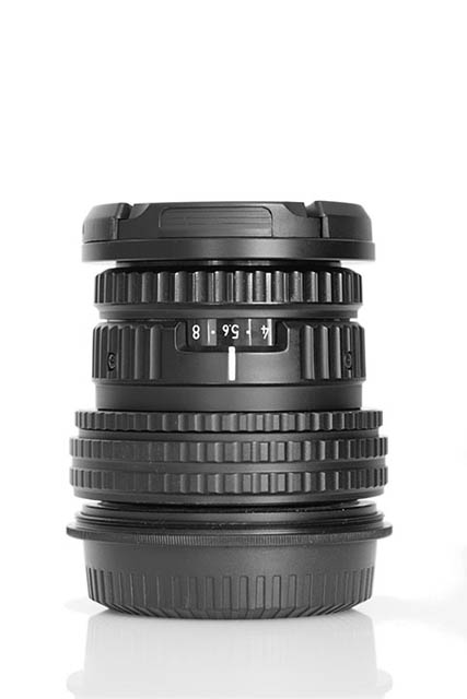 Photo of a camera lens against a white background, taken with the background some distance behind the lens.