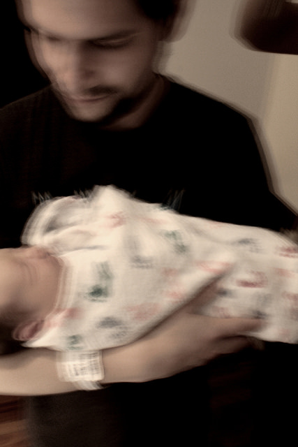Man holding a baby, image blurred from camera shake