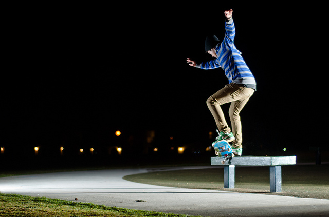 Skateboader at night, lit with flash so the subject stands out against the dark night sky
