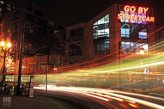 Light trails left by traffic traveling along a street captured by using camera on a tripod combined with a slow shutter speed