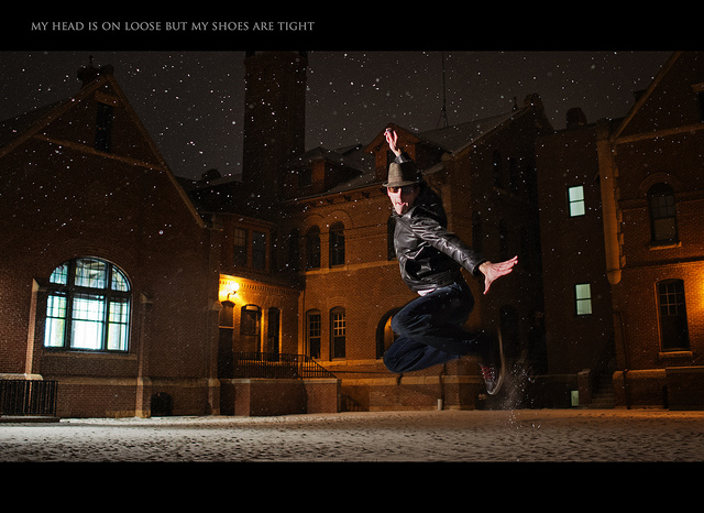Man jumping in the snow at night - background and subject both exposed nicely by combining ambient light exposure with flash