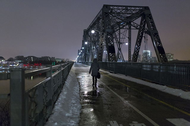 Person walking across a large bridge at night, captured using a high ISO setting