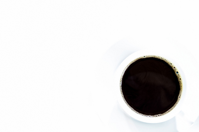 High key photo looking down at a cup of black coffee against a white background. Captured in-camera, with no post-processing.