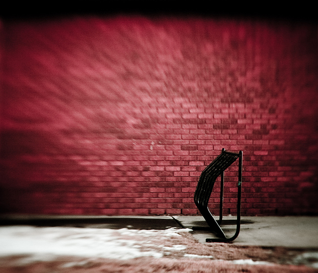 Photo of a bike rack with a brick wall in the background taken with a lensbaby selective focus lens. The image becomes increasgly blurry towards the corners.