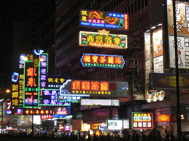Neon signs jutting out from shops in Hong Kong at night