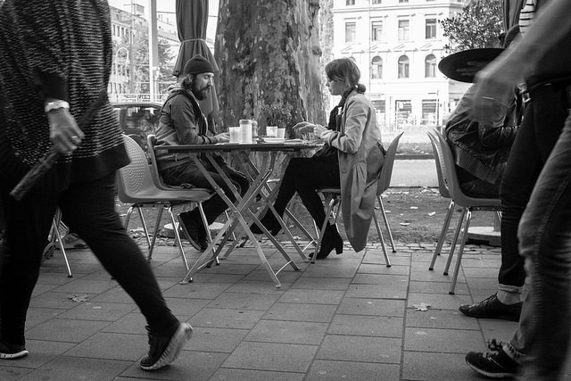 Street photography of people using outdoor seating at a cafe in Cologne