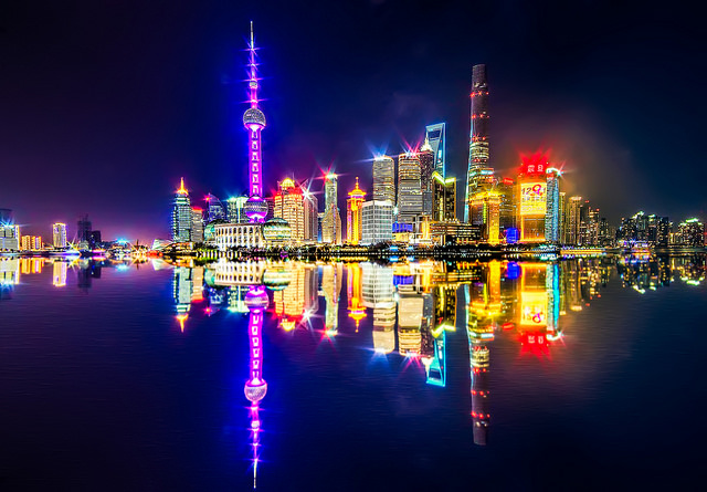 The Shanghai skyline at night, with the buildings reflected in the water of the Huangpu river