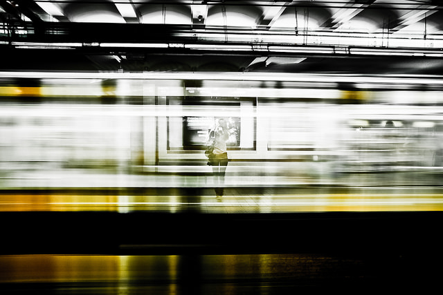 Photo looking at a person across the tracks partially obscured by the blur of a train travelling along the track