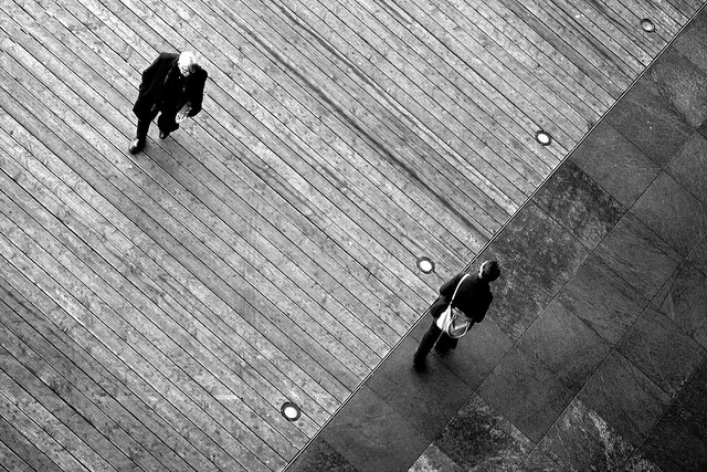 Photo taken from above of someone walking across a piece of wood panelled flooring in the top left half of the image. In the bottom right half of the image another person is walking in the opposite direction on a stone tiled floor.
