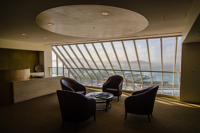 Interior shot of the waiting room of a law firm. Four brown chairs are placed around a small round table. Behind them is a large window giving a view over San Fransico far below. On the left of the image is the reception desk.
