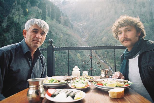 Two men eating a meal at a table with a mountain valley behind them