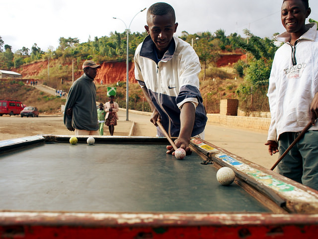 Playing pool with golf balls outdoors on a street in Madagascar