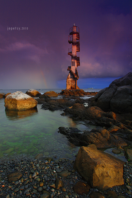 Seascape photo taken with a wide angle lens. The edge of the shore with a large rock is visible in the foreground. On the right of the image a line of rocks leads your eyes across the water to a tall beacon tower at the center of the image. In the background are storm clouds and a rainbow.