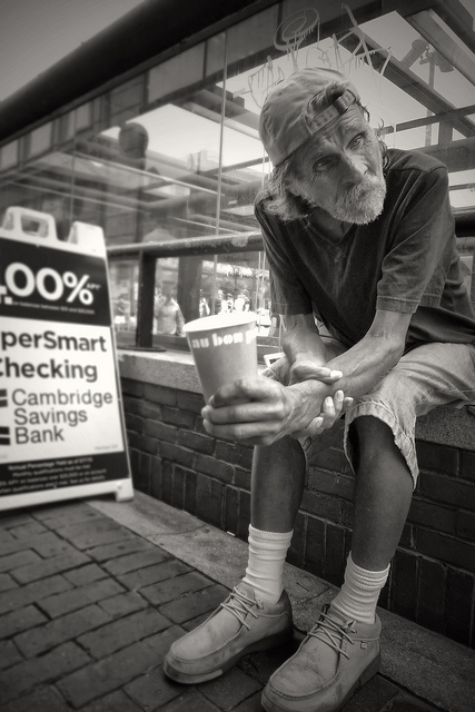 Photo of a beggar sat next to a sign for a bank, shot from the hip
