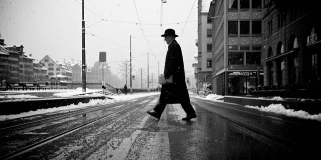 Candid Street photo of a man crossing the street in the snow, taken with a small camera paired with a small lens