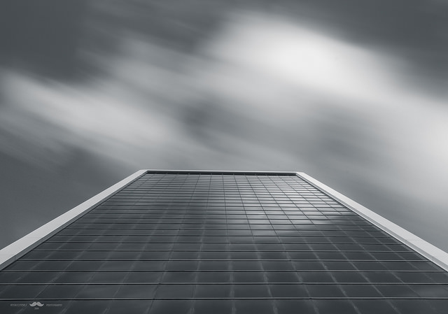 Slow shutter speed used to capture the movement of blurred clouds passing above an office building