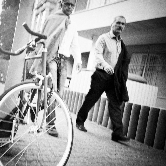 Two people walking past a parked bike - example of Are-bure-boke style photography