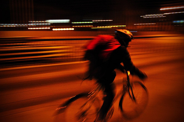 Panning with a moving cyclist at night - the lights in the background blur into streaks, emphasizing the cyclist's movement