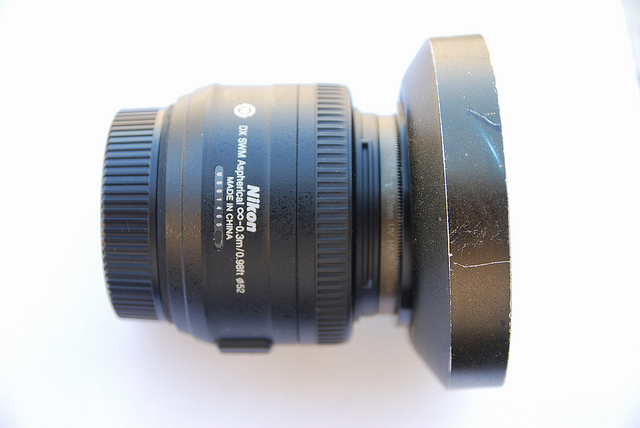 Nikkor 35mm ƒ 1.8 DX lens with lens hood that's had a few bumps and knocks