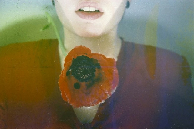 Portrait and red poppy flower floating above, taken on film