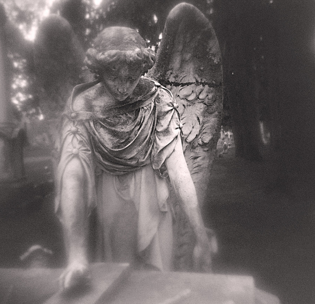 An intentionally soft photo of an angel statue in a graveyard. The softness gives the image an ethereal feeling.